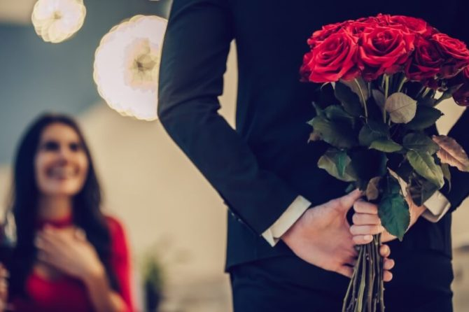 Image of a man holding a dozen red roses with a lady in the background holding a glass of red wine and smiling